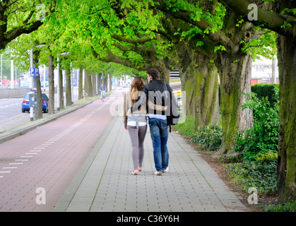 Rotterdam, Netherlands. Young couple walking down avenue of trees - Stock Photo