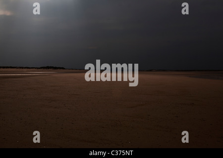 A ray of sun breaks through the clouds at a North Norfolk beach - Stock Photo