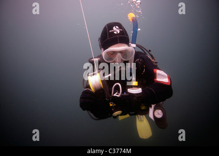 A female diver monitors her computer as she carries out a safety-stop with a deployed DSMB after a dive. - Stock Photo