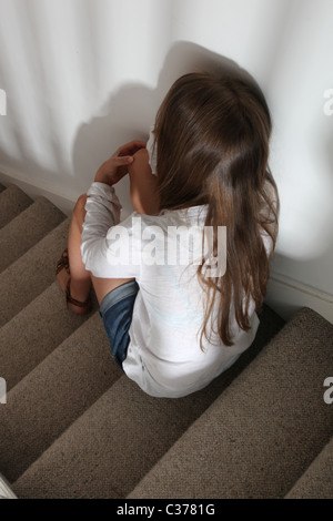 Teenage girl sitting on the stairs alone and upset. - Stock Photo