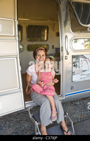 woman and girl in door of camper - Stock Photo