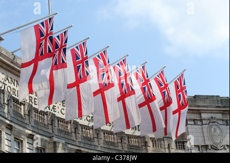 A view looking up at a row of white ensign flags flying over Admiralty Arch in London - Stock Photo