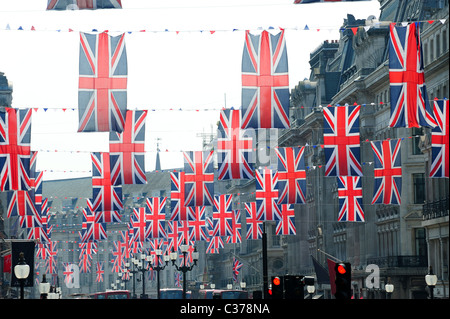 View looking up at rows of many union jack flags hanging above Regent Street London - Stock Photo