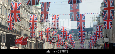 View looking up at lines of many union jack flags hanging above Regent Street London - Stock Photo