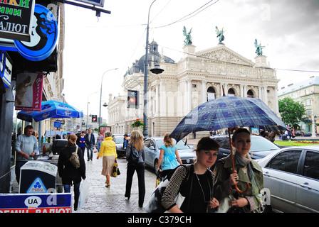 Rainy street scene with Lviv Opera House in background, Ukraine - Stock Photo