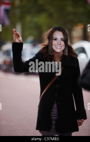 Woman waving wearing a Kate Middleton mask on the mall - Stock Photo