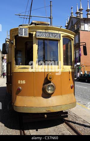 A historic tram runs along a scenic route in central Porto, Portugal. - Stock Photo