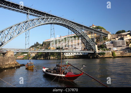 Rabelo Boats float on the River Douro under the King Luis I Bridge at Porto, Portugal. - Stock Photo