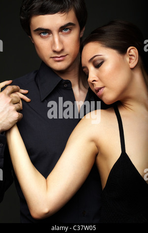 Portrait of elegant girl with handsome man looking at camera on black background - Stock Photo