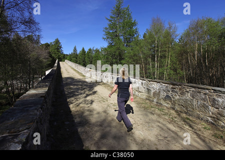 Walker crossing newly refurbished (2011) old Invercauld Bridge over the River Dee near Braemar in Aberdeenshire, - Stock Photo