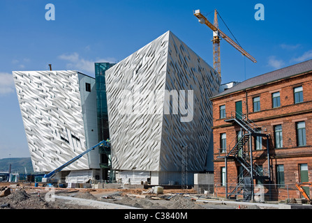 The new Titanic Museum under construction in Belfast, the original Titanic drawing office is on the right. - Stock Photo