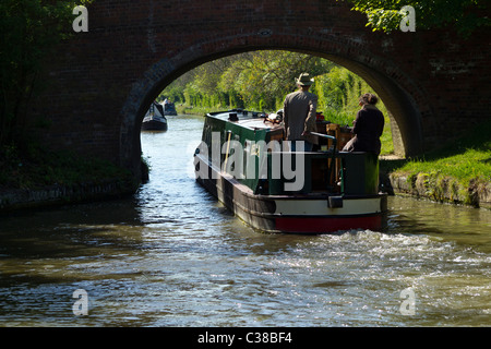 Longboat going under Bridge Grand Union Canal - Stock Photo