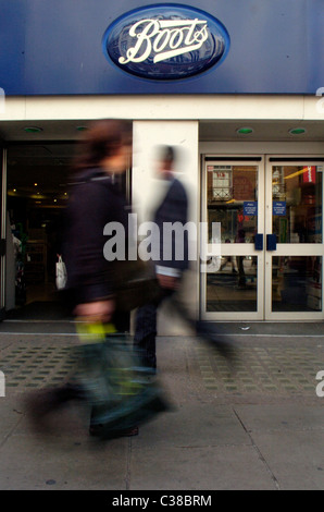 People walking past a Boots store on Oxford Street, London. - Stock Photo