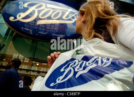 A woman with a Boots shopping bag on Oxford Street, London Stock ...