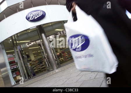 A Boots customer leaving a store carrying their purchases in a branded bag. - Stock Photo
