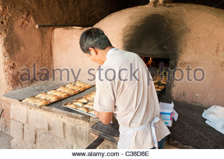 Peruvian baker removes Empanadas (small meat pies) from a wood-fired adobe oven. Pisac, Peru. - Stock Photo