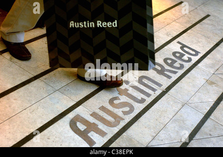 A man leaving an Austin Reed store with his purchases.