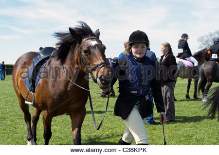 Dilwyn village show, Herefordshire, UK. Young girl leading a pony behind the scenes at gymkhana, England. - Stock Photo