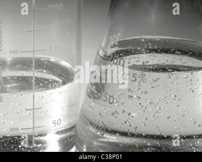 Beakers In Lab With Boiling Liquid & Air Bubbles - Stock Photo