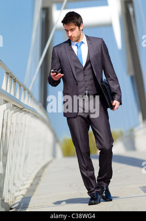 Man walking looking at phone - Stock Photo