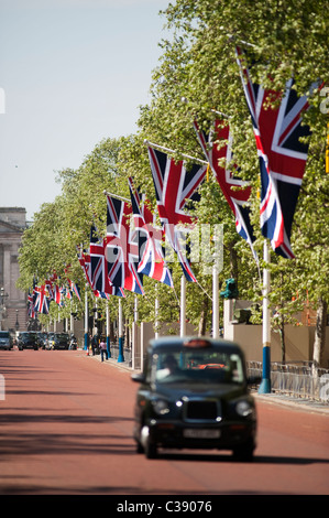 View along the Mall towards Buckingham Palace in London with a black taxi and union jacks on flagpoles - Stock Photo