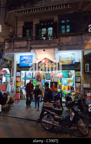 Vertical night time view of a tourists outside a gallery selling big paintings on Hang Be street in the Old Quarter - Stock Photo