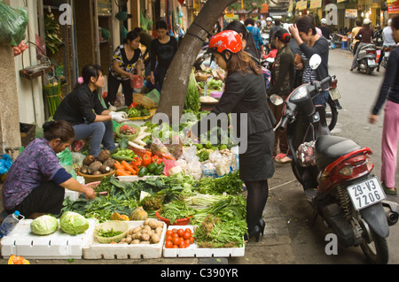 Horizontal view of disorganised chaos on a street in the Old Quarter in Hanoi with fruit and veg stalls lining the - Stock Photo