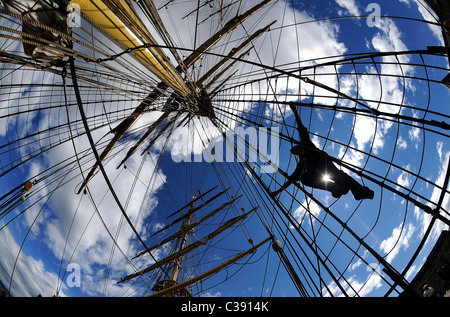 A crew member climbs the rigging on the Danish tall ship Georg Stage as it sails up the River Clyde in Scotland. - Stock Photo