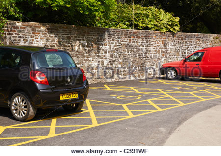 a motor car and a red van parked in a disabled parking bay - Stock Photo
