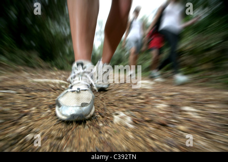 Close up of foot in motion as it strikes the ground as adults walk along a forest trail - Stock Photo
