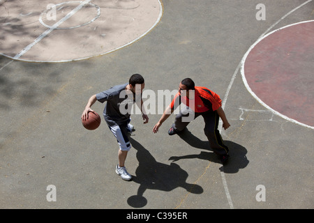 Young adults playing street basketball in Riverside Park, New York City. - Stock Photo
