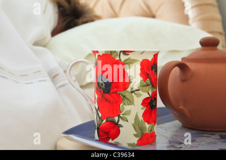 Everyday image of a morning mug of tea and teapot on a bedside table with a person sleeping in bed having a duvet - Stock Photo