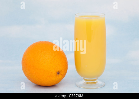 One glass of fresh orange juice with a whole orange containing vitamin C against a blue sky background - Stock Photo