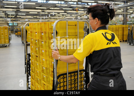 An employee with a trolley in a postal sorting centre, Berlin, Germany - Stock Photo