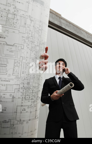 Woman holding building plans while man talks on phone - Stock Photo