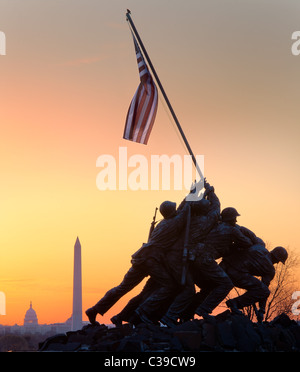 The Marine Corps War Memorial in Arlington, VA at sunrise with the US Capitol and Washington Monument visible - Stock Photo