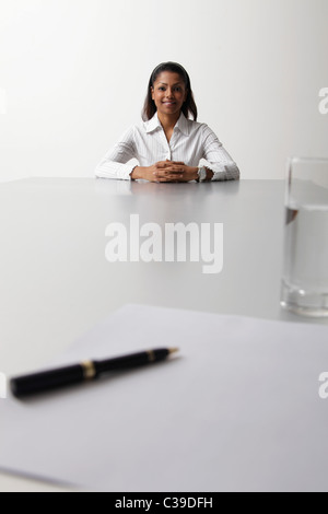 young woman sitting at end of the table being interviewed - Stock Photo