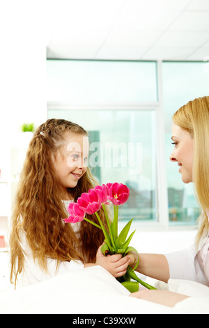 Adorable girl giving bunch of beautiful tulips to her mother - Stock Photo