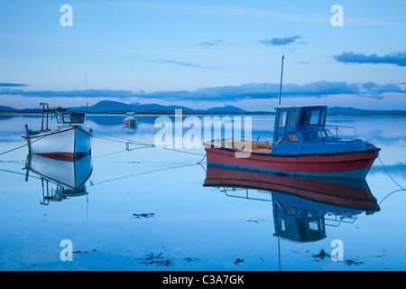 Fishing boats reflected at dusk in Clew Bay, County Mayo, Ireland. - Stock Photo