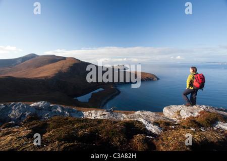 Walker looking across Lough Nakeeroge to Croaghaun, Achill Island, County Mayo, Ireland. - Stock Photo