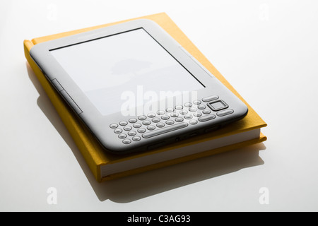 Amazon Kindle ebook reader on traditional book FOR EDITORIAL USE ONLY - Stock Photo