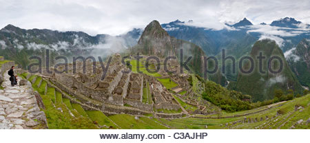 Two tourists looking at Machu Picchu complex early on a foggy morning. Machu Picchu, Peru. - Stock Photo