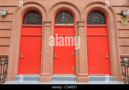 Three red doors at the entrance of a building. - Stock Photo