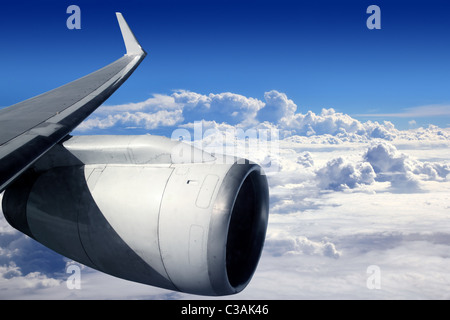 airplane wing aircraft turbine flying blue sky white clouds - Stock Photo