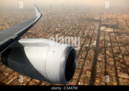 airplane wing aircraft turbine flying over Mexico DF city - Stock Photo