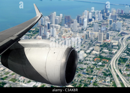 airplane wing aircraft turbine flying on Miami downtown - Stock Photo