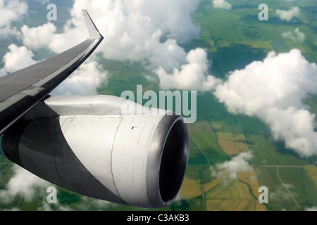airplane wing aircraft turbine flying over agriculture fields - Stock Photo