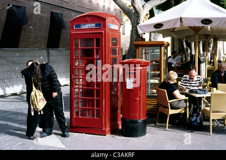 Young couple enjoying a private moment next to a British colonial phone booth and pillar box at Palace Square in - Stock Photo