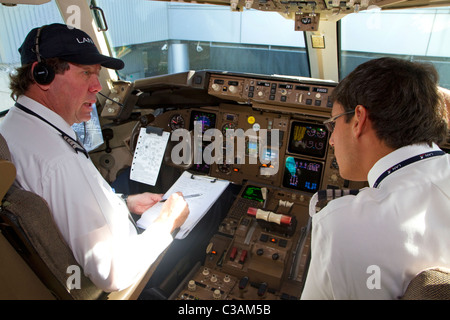 Pilot and first officer reviewing a pre-flight checklist in the cockpit of a Boeing 767 aircraft. - Stock Photo