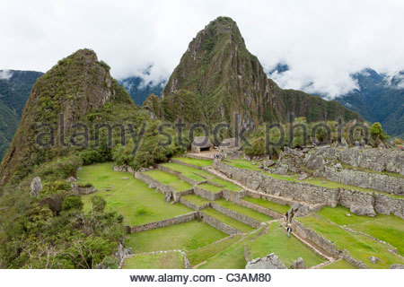 View of the Plaza Principal (main plaza) at Machu Picchu complex with Wayna Picchu mountain in the background. - Stock Photo